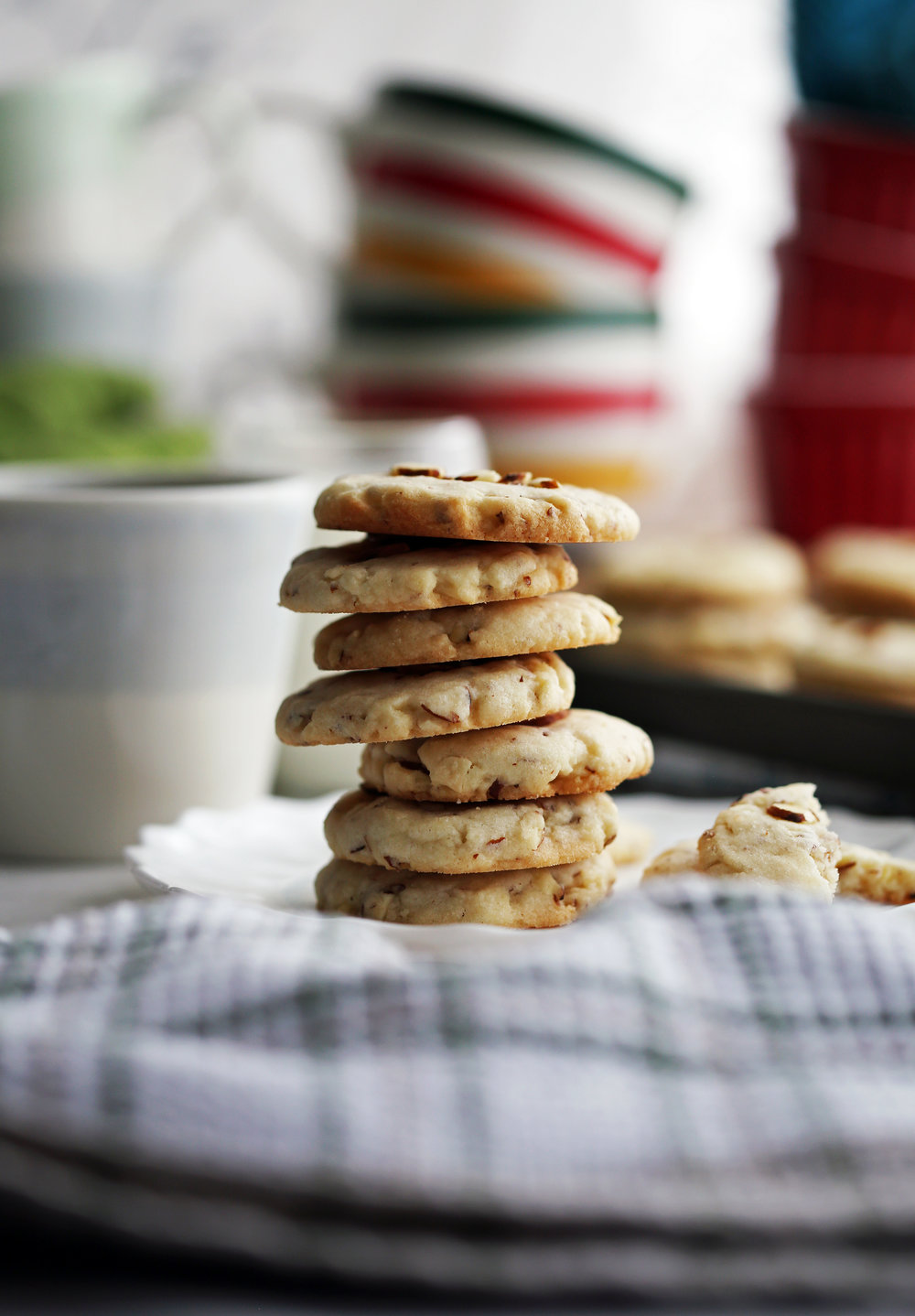 A stack of seven crunchy almond cookies on a white plate.