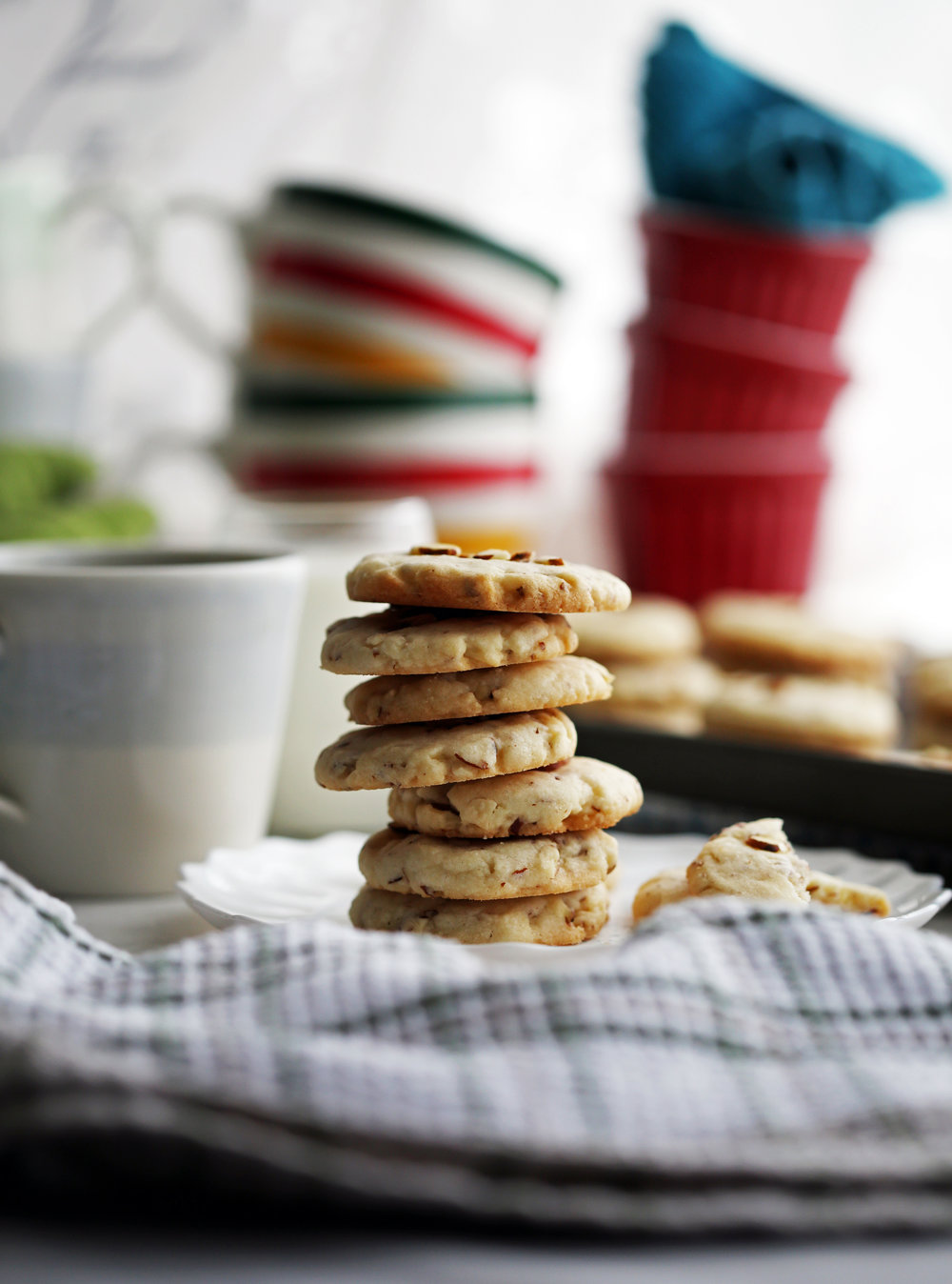 A stack of seven crunchy almond cookies on a white plate with cookies and coffee in the background.
