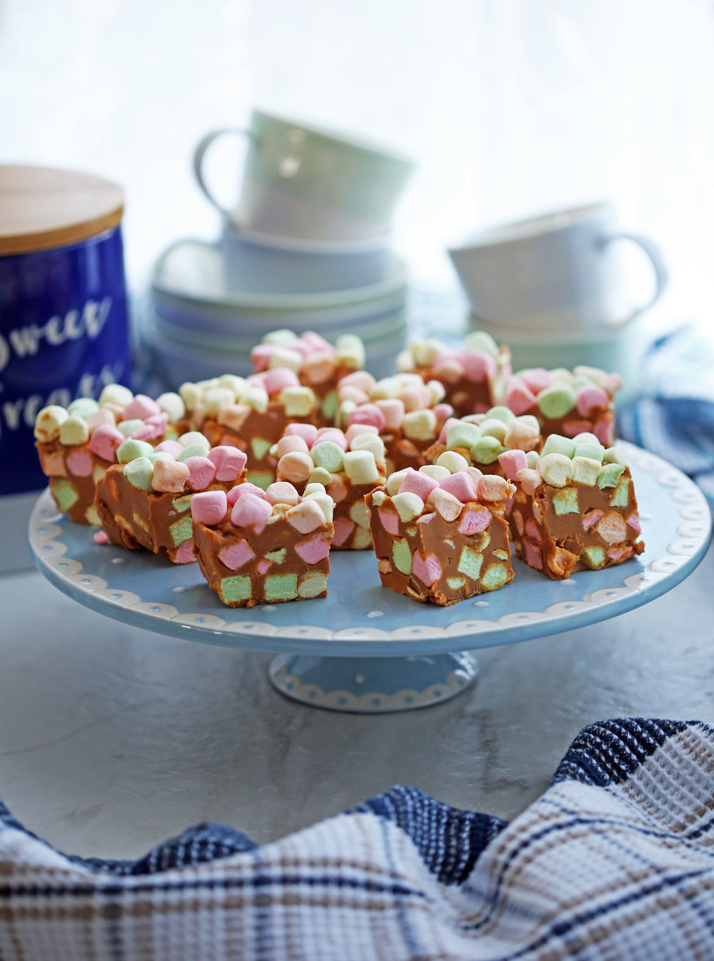 Peanut butter butterscotch marshmallows bars also known as confetti bars on a blue cake stand.