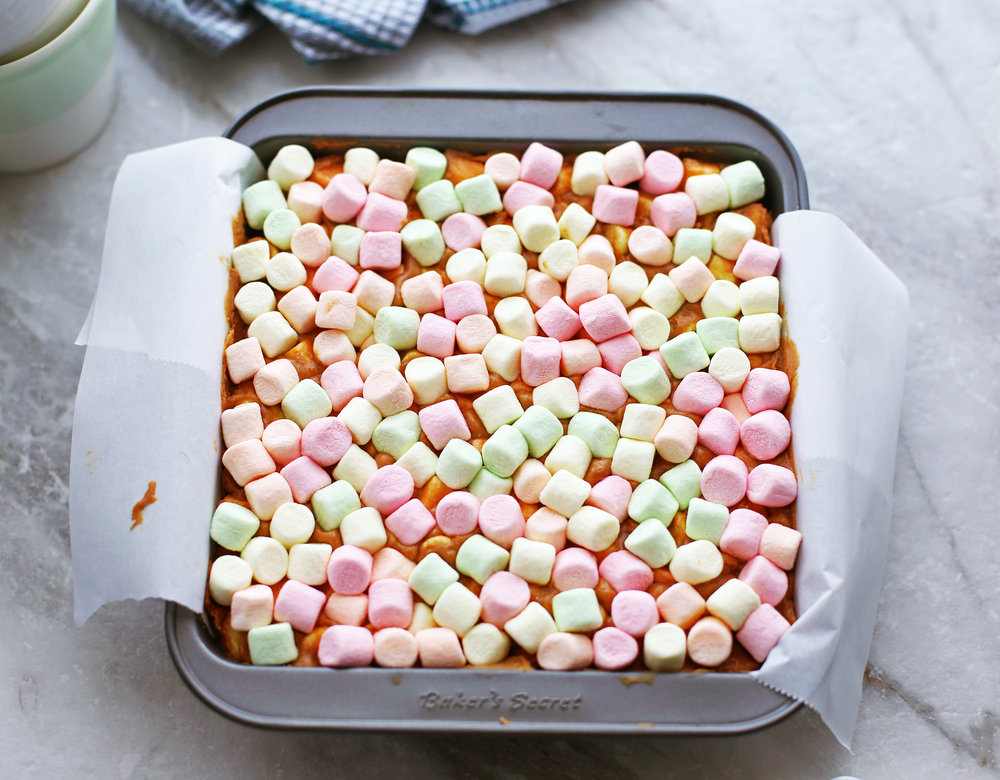 Combined confetti bar ingredients in a square parchment paper lined baking dish.
