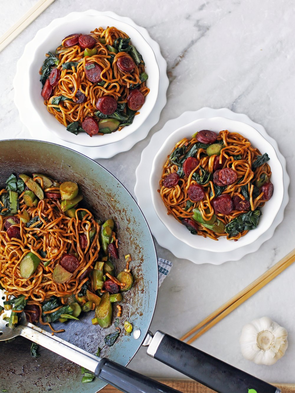 Two bowls of Lo mein noodles with Chinese sausage and gai lan and more in a large wok.