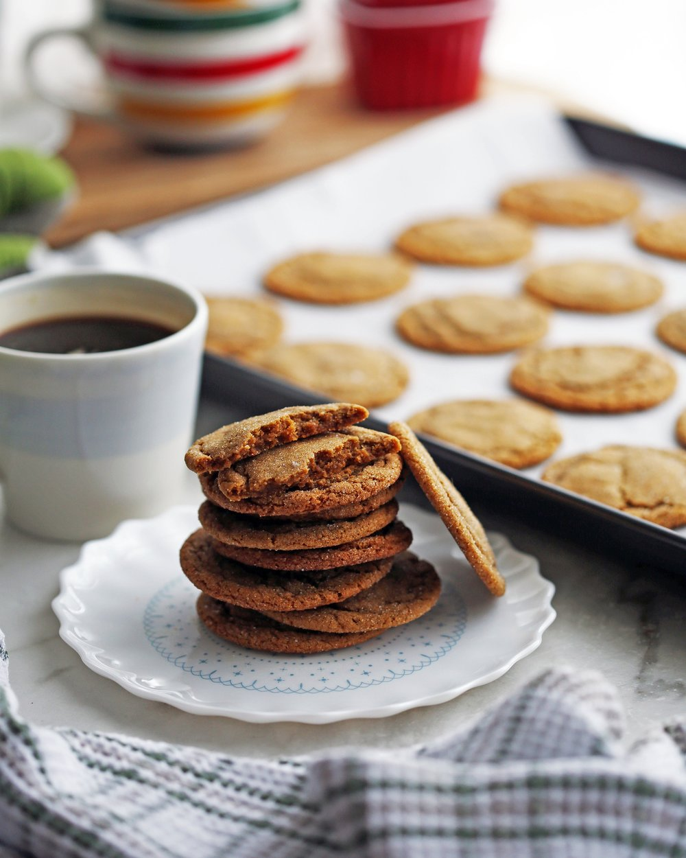 Stacked classic chewy gingersnap cookies on a plate with more cookies on a baking sheet in the background.