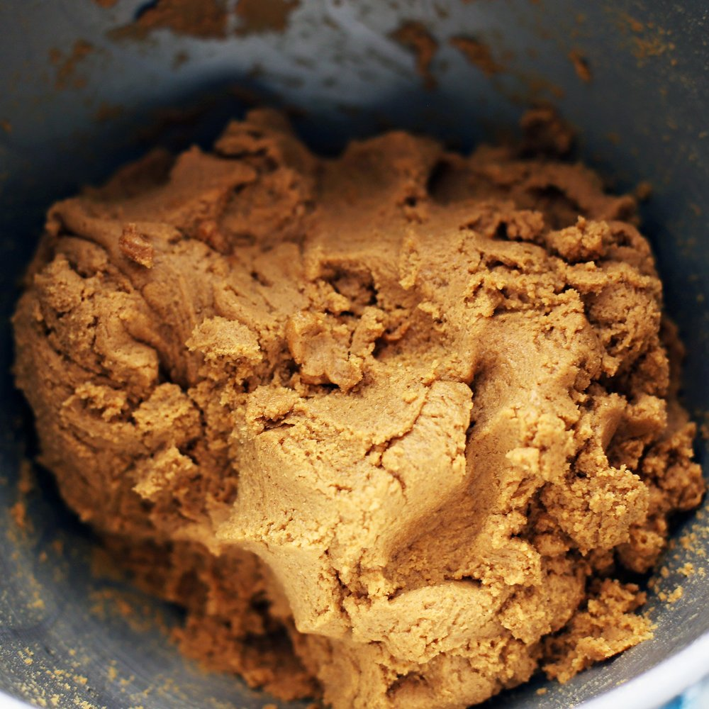 Soft gingersnap cookie dough in a metal mixing bowl.