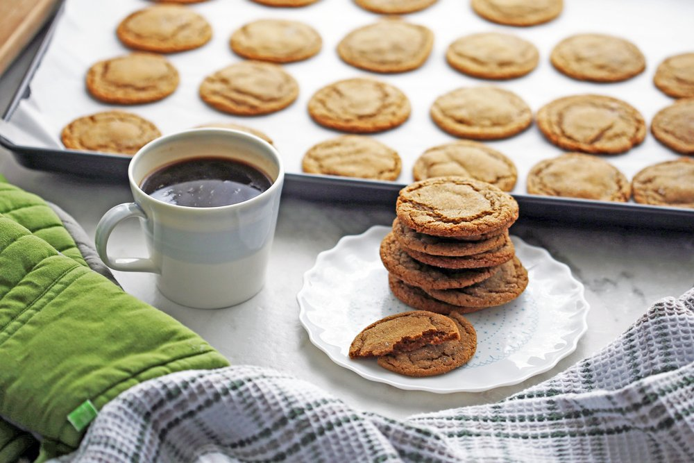 A side view of a plate of chewy gingersnap cookies with a cup of coffee and cookies on a baking sheet in the background.