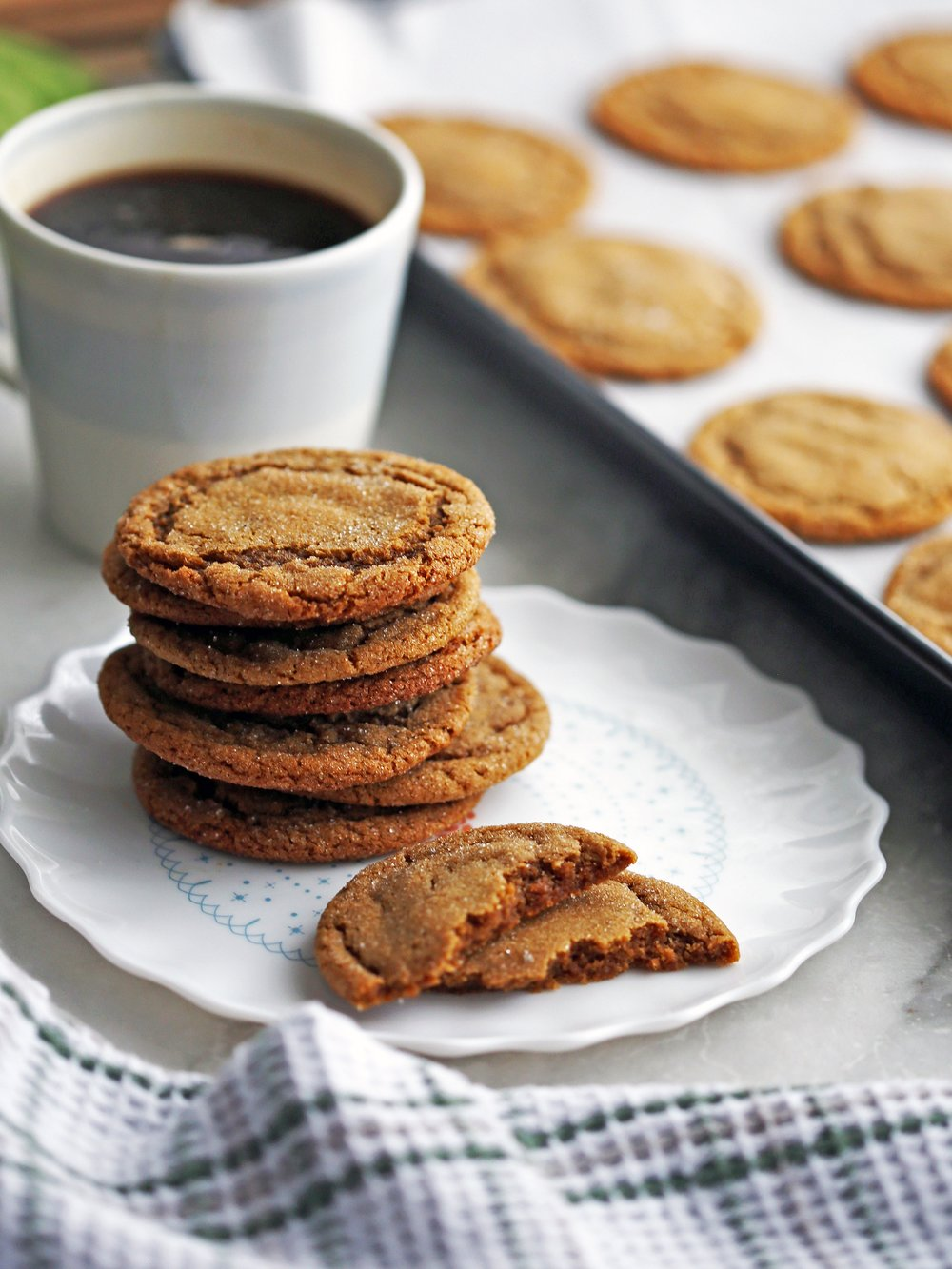 A closeup side view of a stack of chewy gingersnap (ginger molasses) cookies with coffee and more cookies in the background.