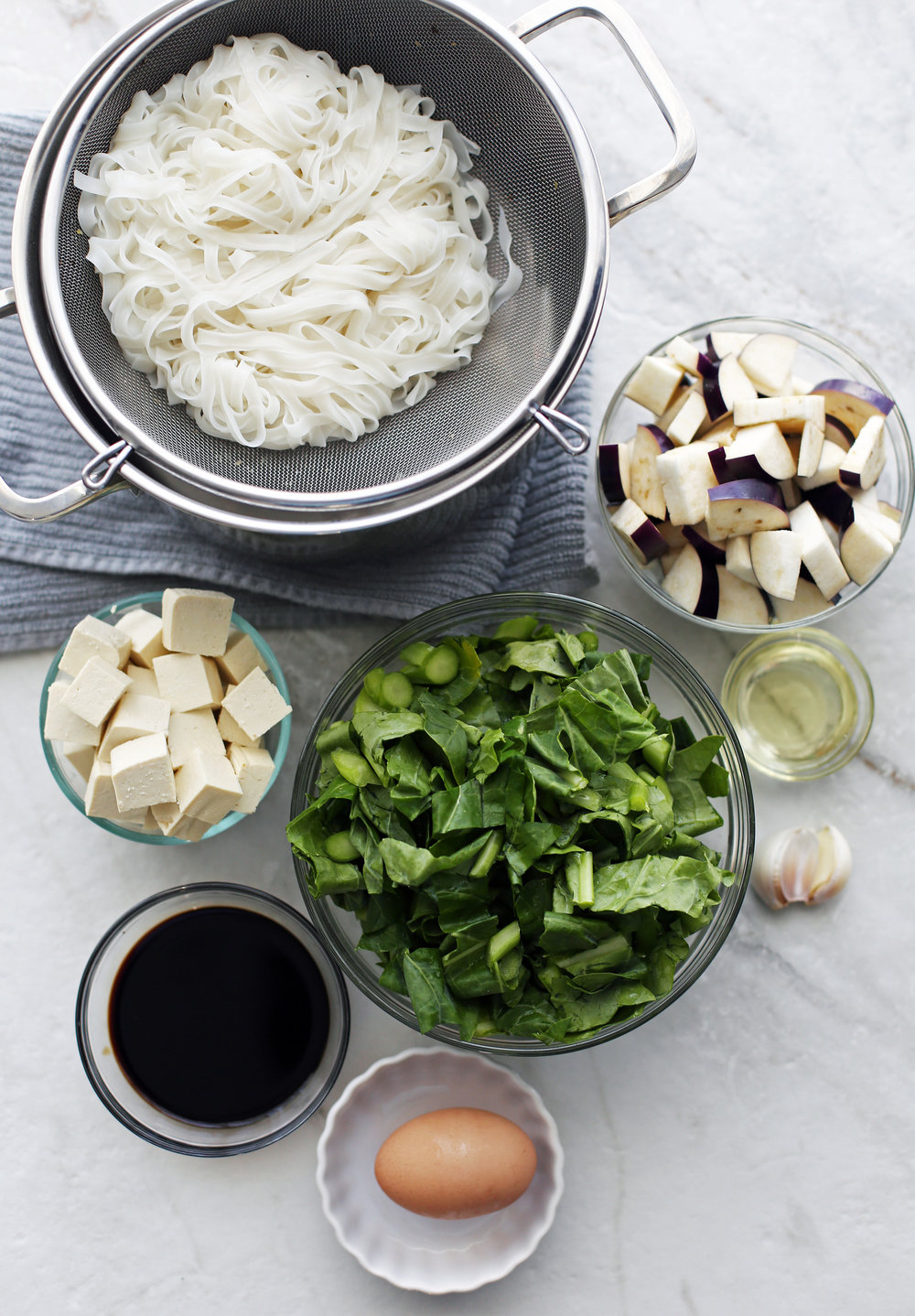 Bowls of cooked rice noodles, tofu, gai lan, eggplants, egg, soy sauce, and garlic.