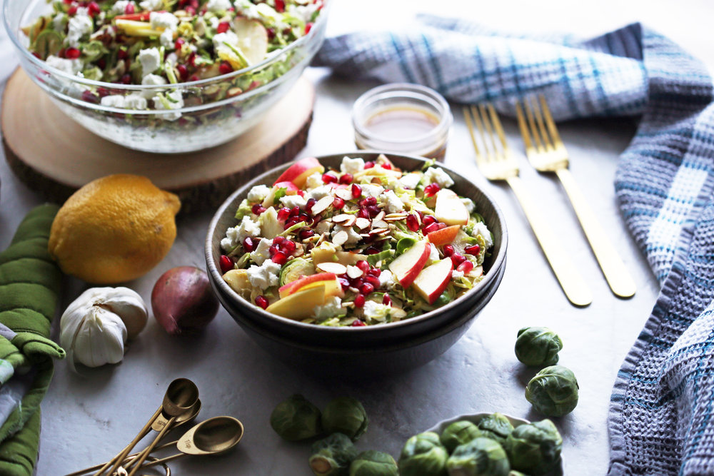 A side angled view of a bowl of shaved Brussels sprouts and pomegranate salad with lemon vinaigrette with more salad in a large glass bowl in the background.