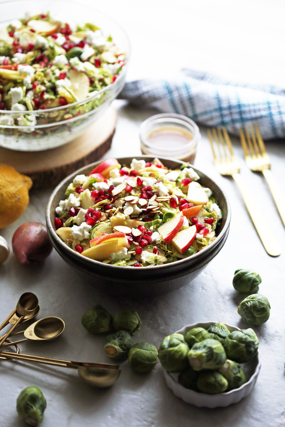 A bowl of shaved Brussels sprouts and pomegranate salad with lemon balsamic vinaigrette.