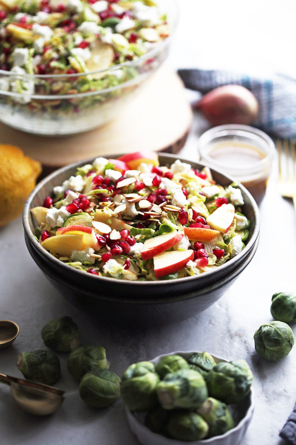 A bowl of shaved Brussels sprouts and pomegranate salad with lemon vinaigrette with more salad in a large glass bowl in the background and raw Brussels sprouts in the foreground.