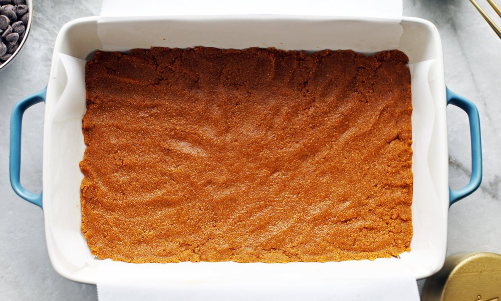 Combined graham cracker crumbs and melted butter pressed into an even layer into a baking dish lined with parchment paper.