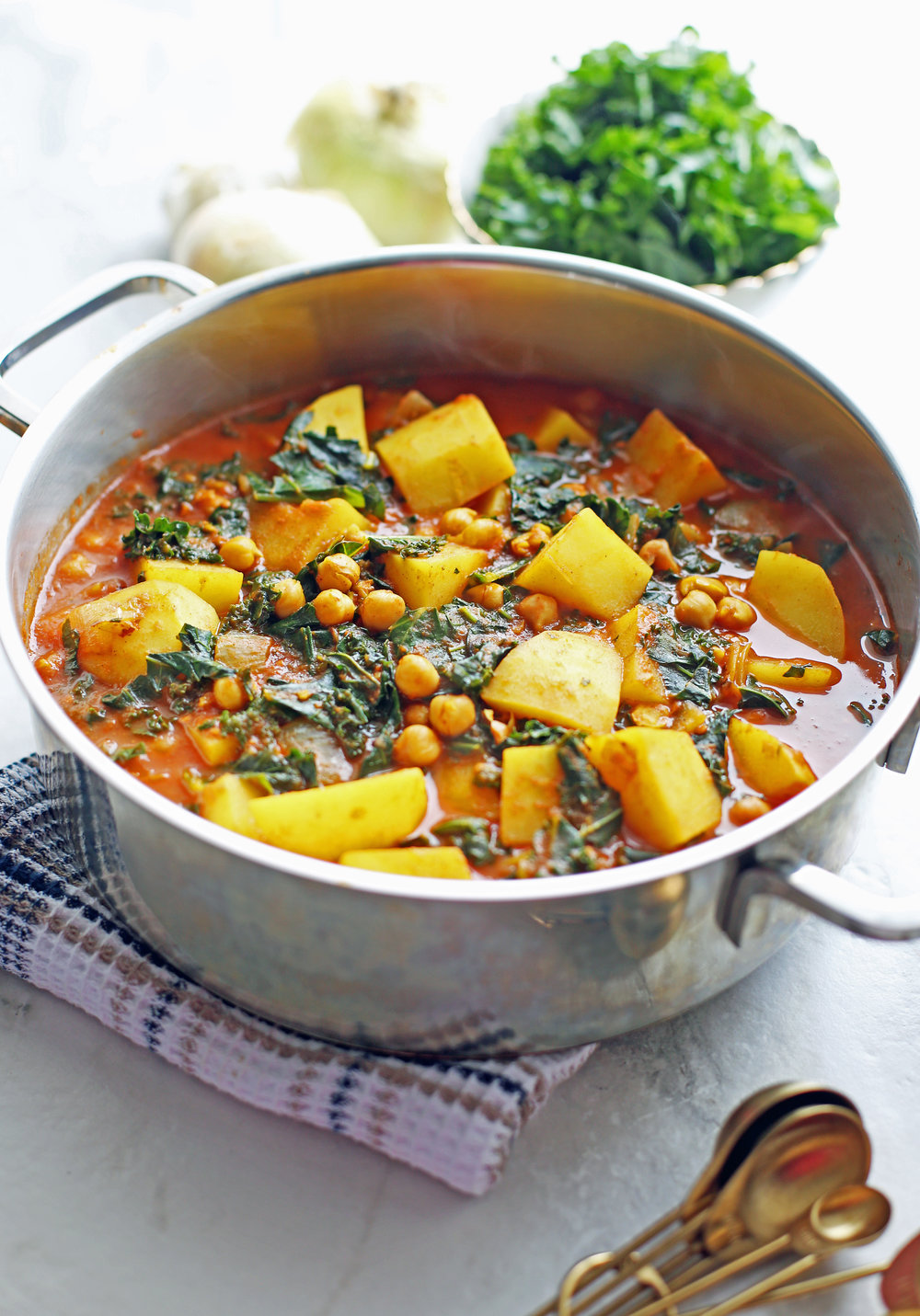 A side view of Spicy Chickpea Kale and Potato Curry in a large silver pot.