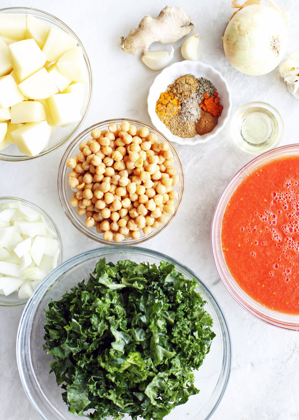 Bowls of kale, chickpeas, potatoes, onions, pureed tomatoes, spices, garlic, and onion.