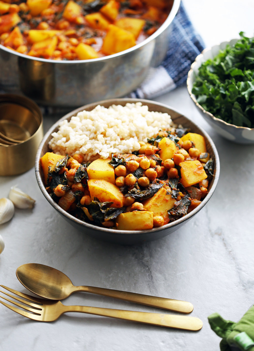 A side angle view of Spicy Chickpea Kale and Potato Curry with rice with a large pot of curry in the background.