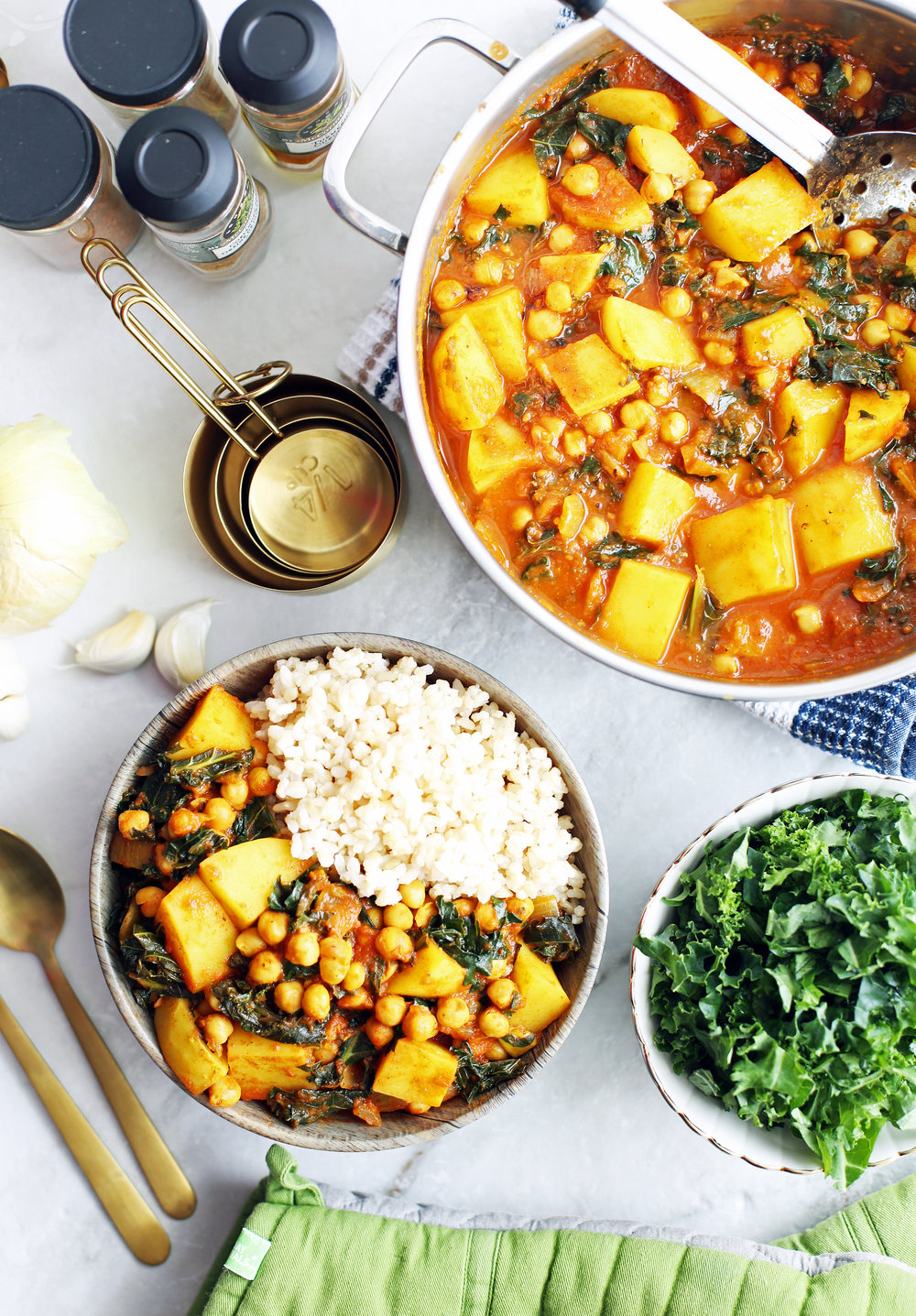 An overhead view of a bowl of chickpea kale and potato curry, a pot of curry, and a bowl of raw kale.
