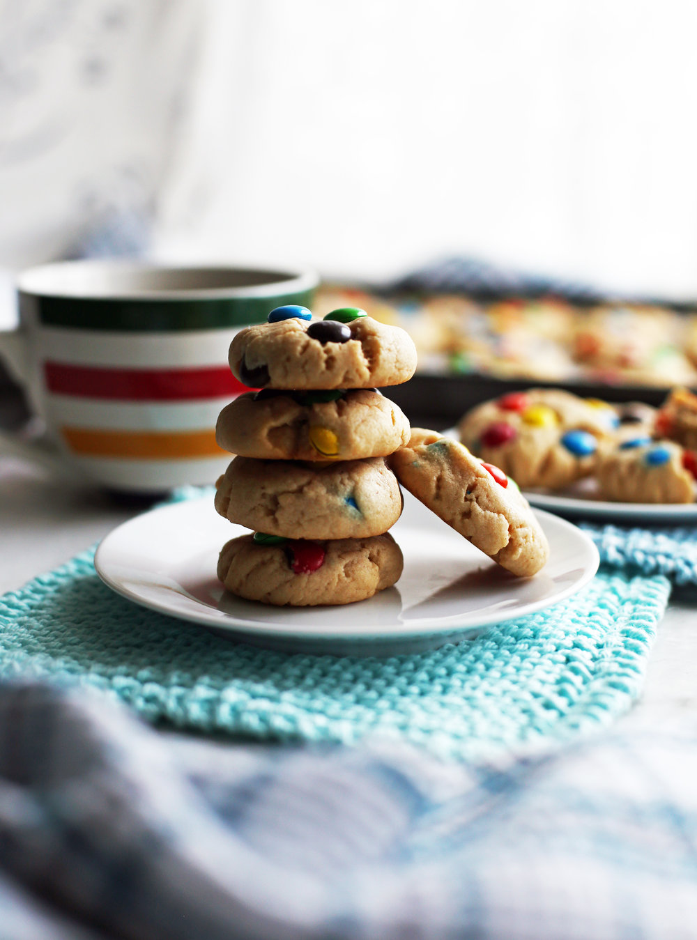 Four stacked peanut butter M&M's cookies on a white plate with more cookies in the background.