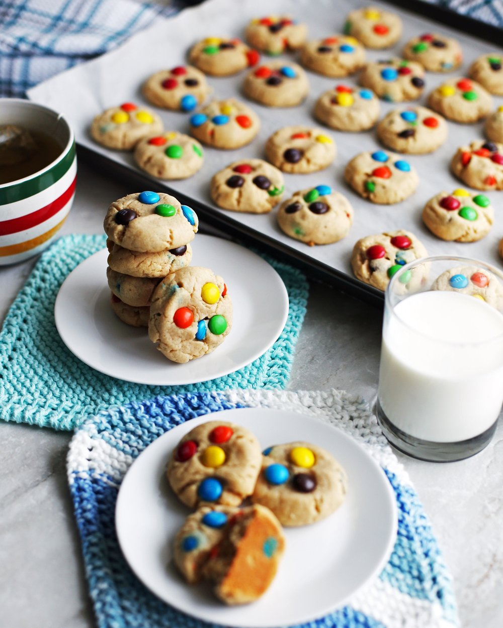 Two plates of Chewy Peanut Butter Cookies with M&M's with cookies on a baking sheet in the background.