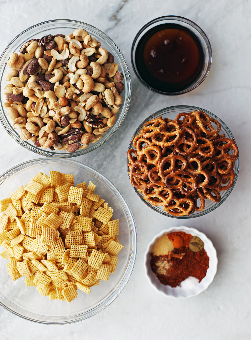 Glass bowls filled with Chex cereal, mini pretzels, mixed nuts, maple syrup, and spices.