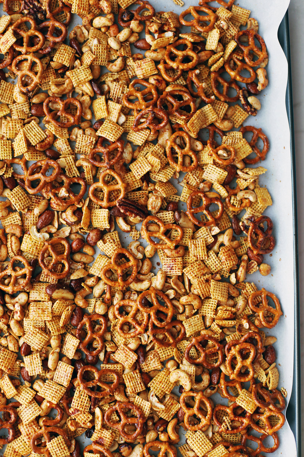 Baked Maple Chili Nuts and Chex Snack Mix on a parchment paper lined baking sheet.