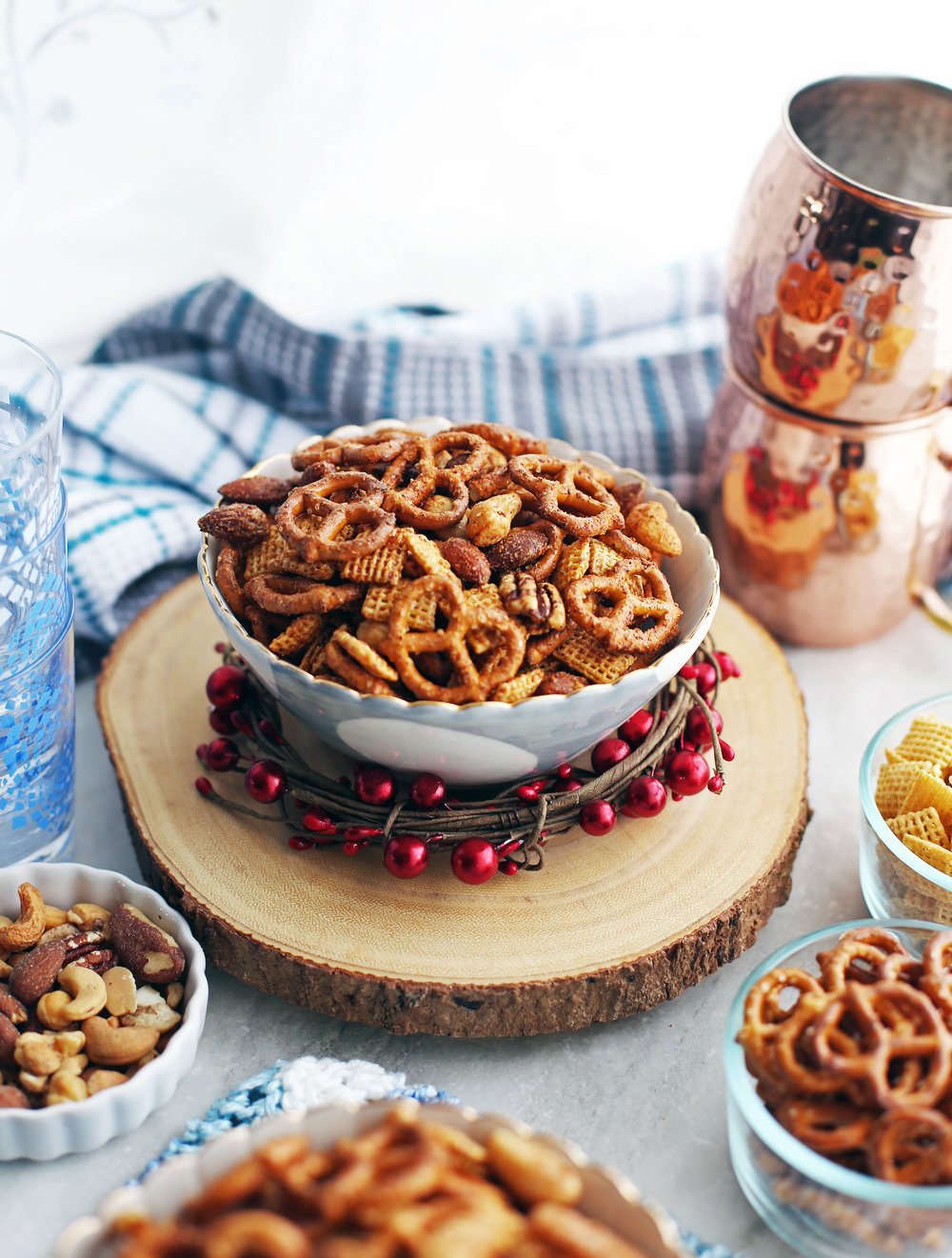 Side shot of a bowl of Maple Chili Nuts and Chex Mix with nuts, pretzels, and Chex cereal in the background.