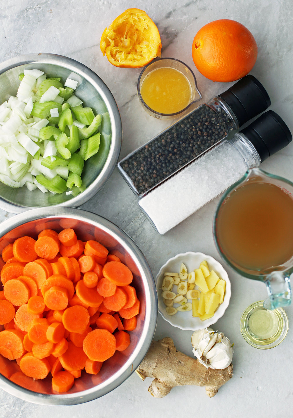 Bowls of carrots, onions, celery, ginger, garlic, vegetable broth, and orange juice along with salt and pepper shakers..