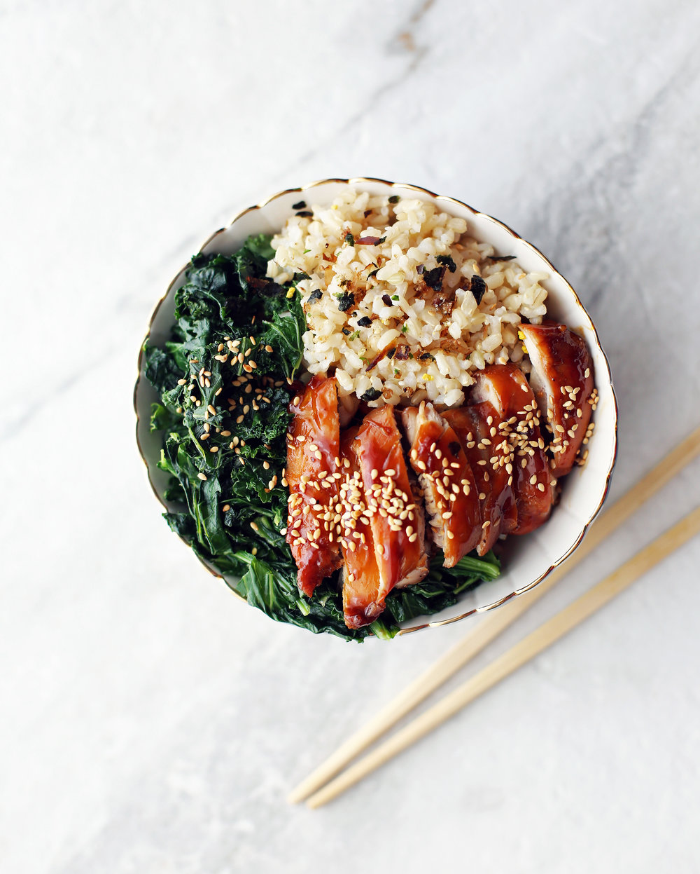 Overhead view of a bowl of sliced teriyaki chicken, sautéed kale, and brown rice topped with furikake.