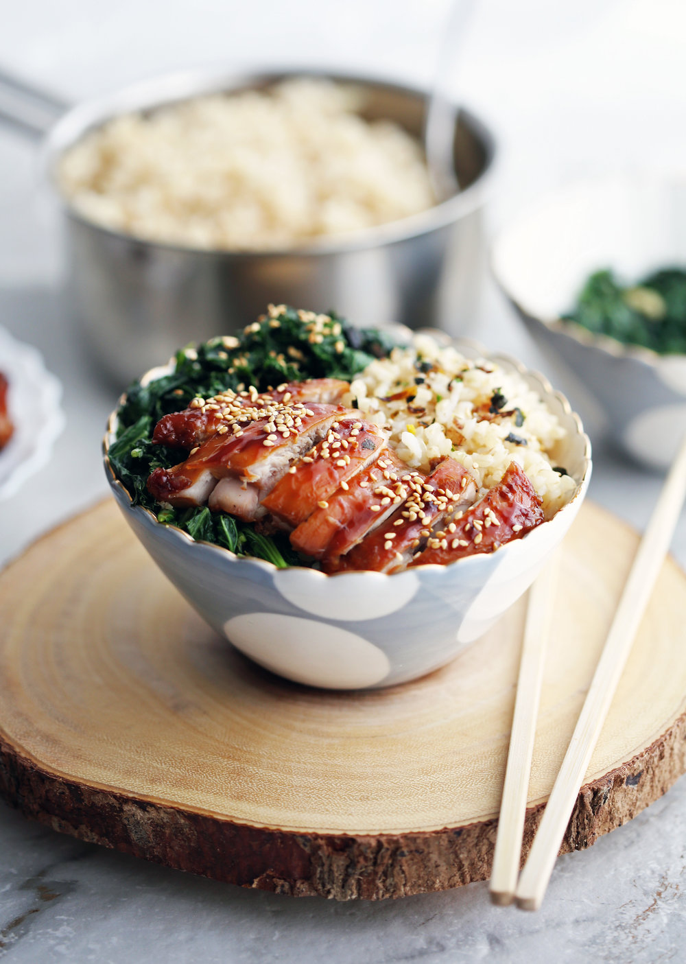 Side view of a teriyaki chicken rice bowl with garlicky kale with chopsticks on a wood slab.