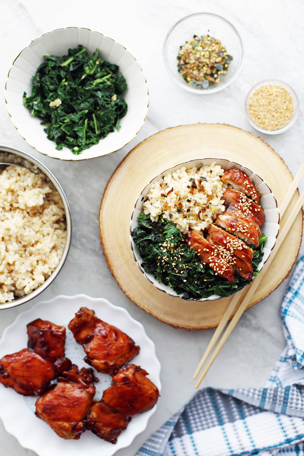 Overhead shot of a bowl of teriyaki chicken with garlicky kale and brown rice, a plate of teriyaki chicken thighs, a bowl of brown rice, and seasonings.