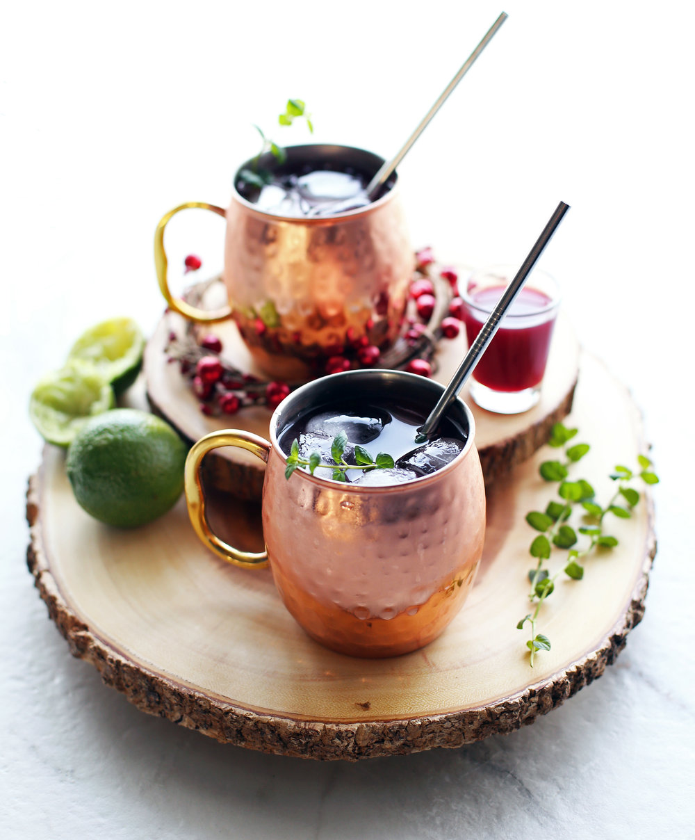 Two Pomegranate Honey Moscow Mule cocktails in copper mugs on two round wood slabs.