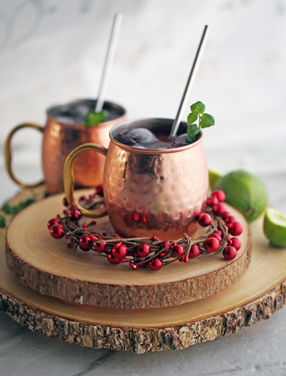 Two Pomegranate Honey Moscow Mule cocktails in copper mugs on wood slabs.