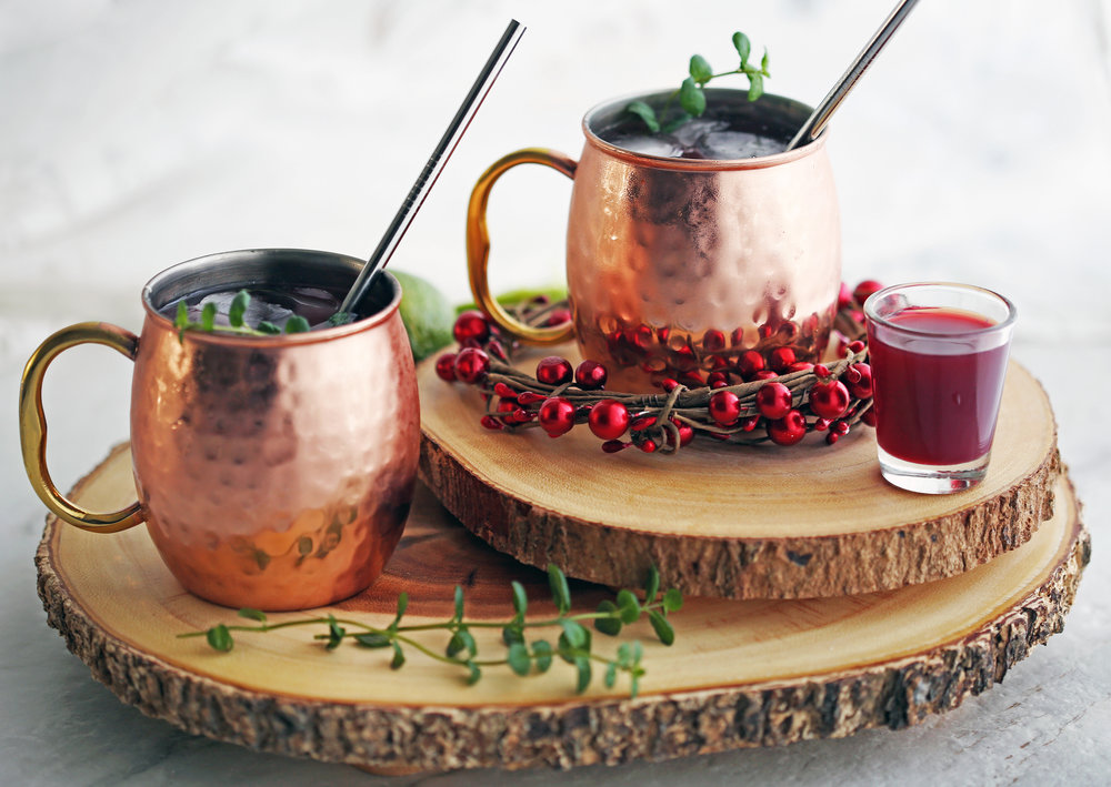 Two Pomegranate Honey Moscow Mule cocktails with mint garnish in copper mugs on two round wood slabs.