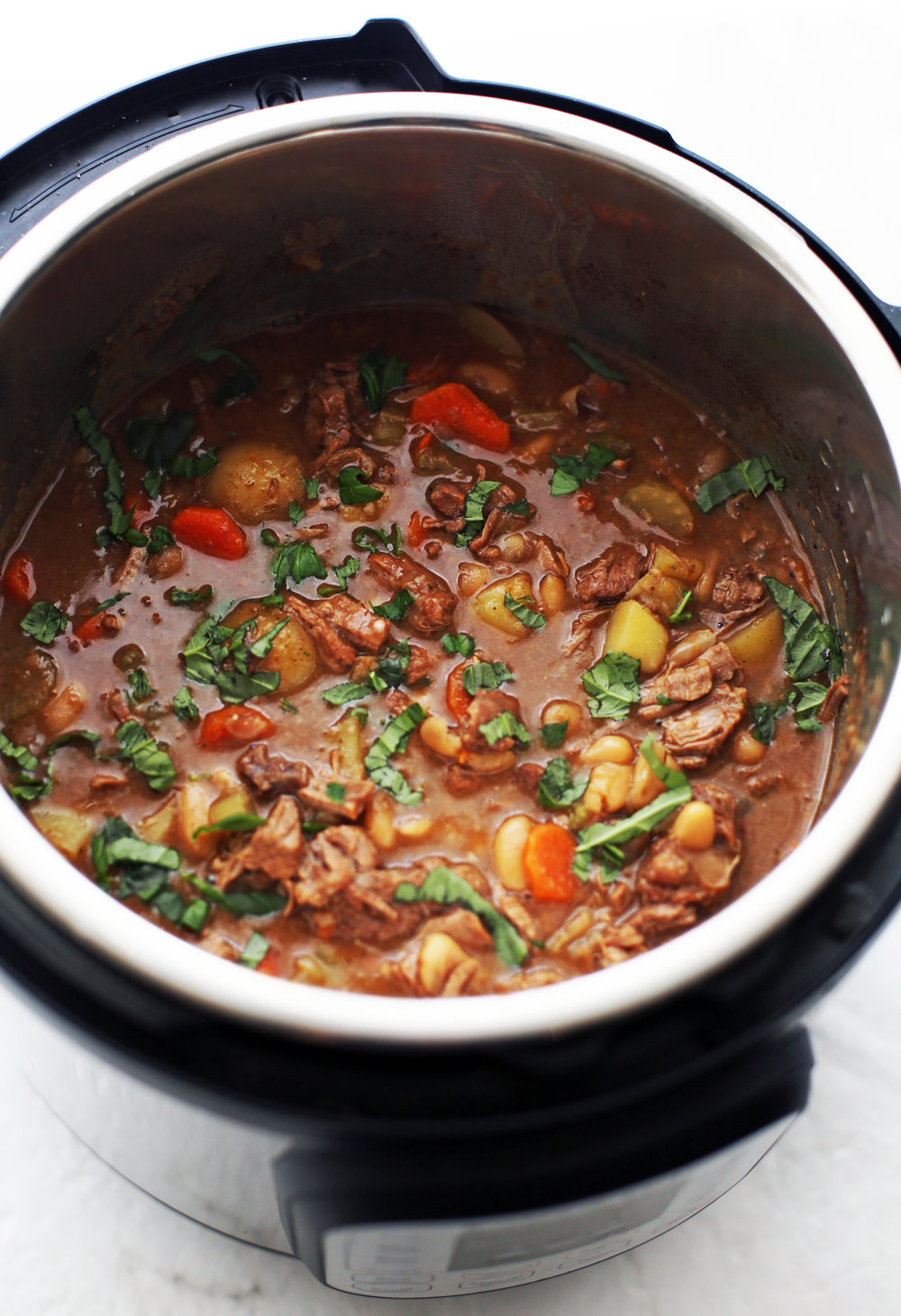 A top view of Chinese Five Spice Beef and Vegetable Stew with green basil on top in the Instant Pot.