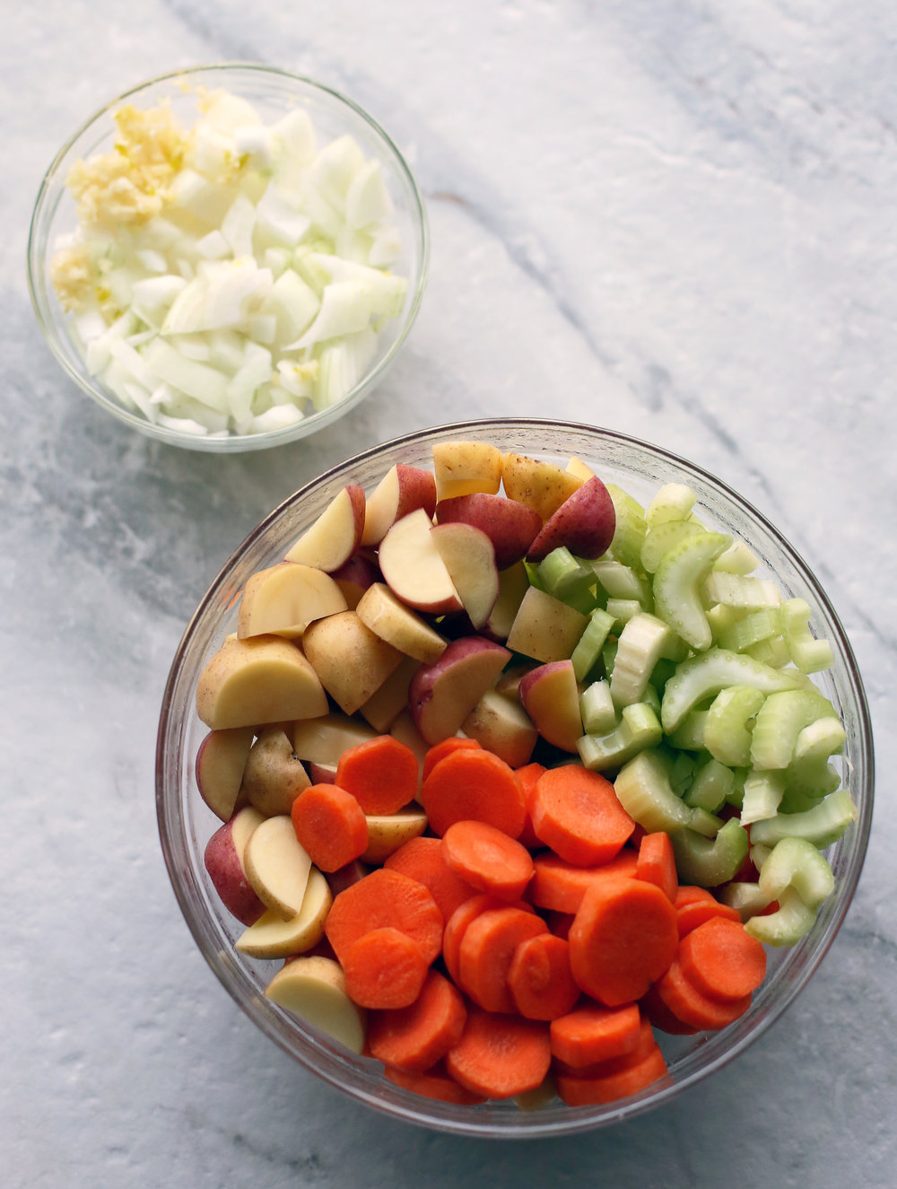 Two glass bowls filled with garlic, onions, carrots, potatoes, and celery.