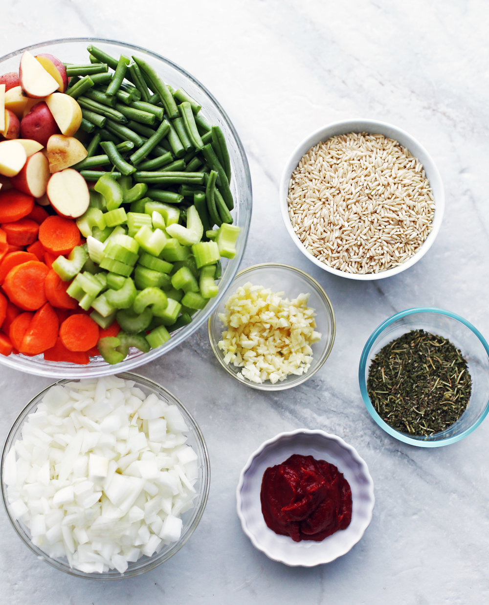 Six glass bowls with green beans, carrots, potatoes, celery, onions, garlic, ginger, brown rice, herbs, and tomato paste.