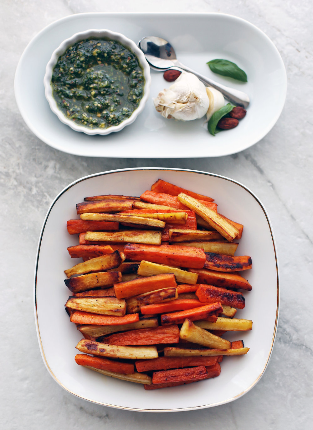 Roasted Balsamic Root Vegetables stacked on a white plate with basil almond pesto in a small bowl with spoons to its side.