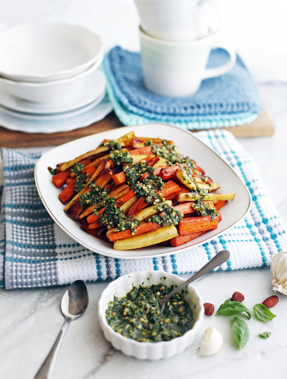 Roasted Balsamic Root Vegetables topped with Basil Almond Pesto on a white plate; more pesto in a small bowl on the side.
