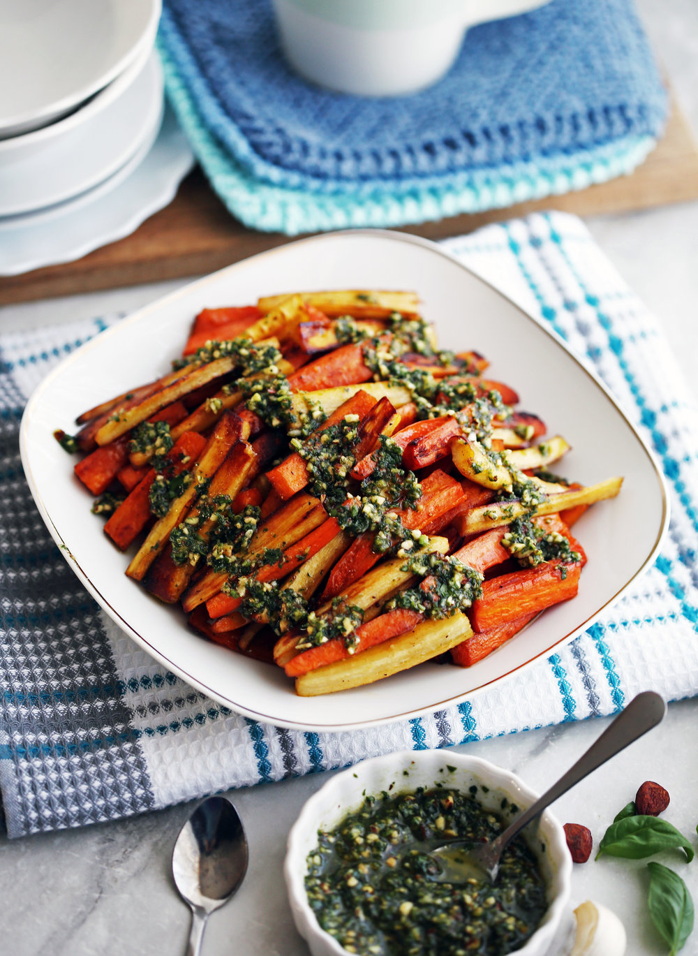 Roasted Balsamic Root Vegetables with Basil Almond Pesto on a white plate; more pesto in a small bowl on the side.