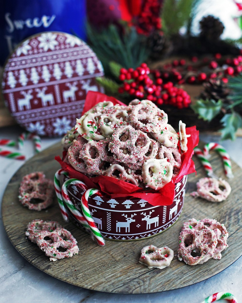 Red and green candy cane chocolate-covered pretzels overflowing in a large red tin.