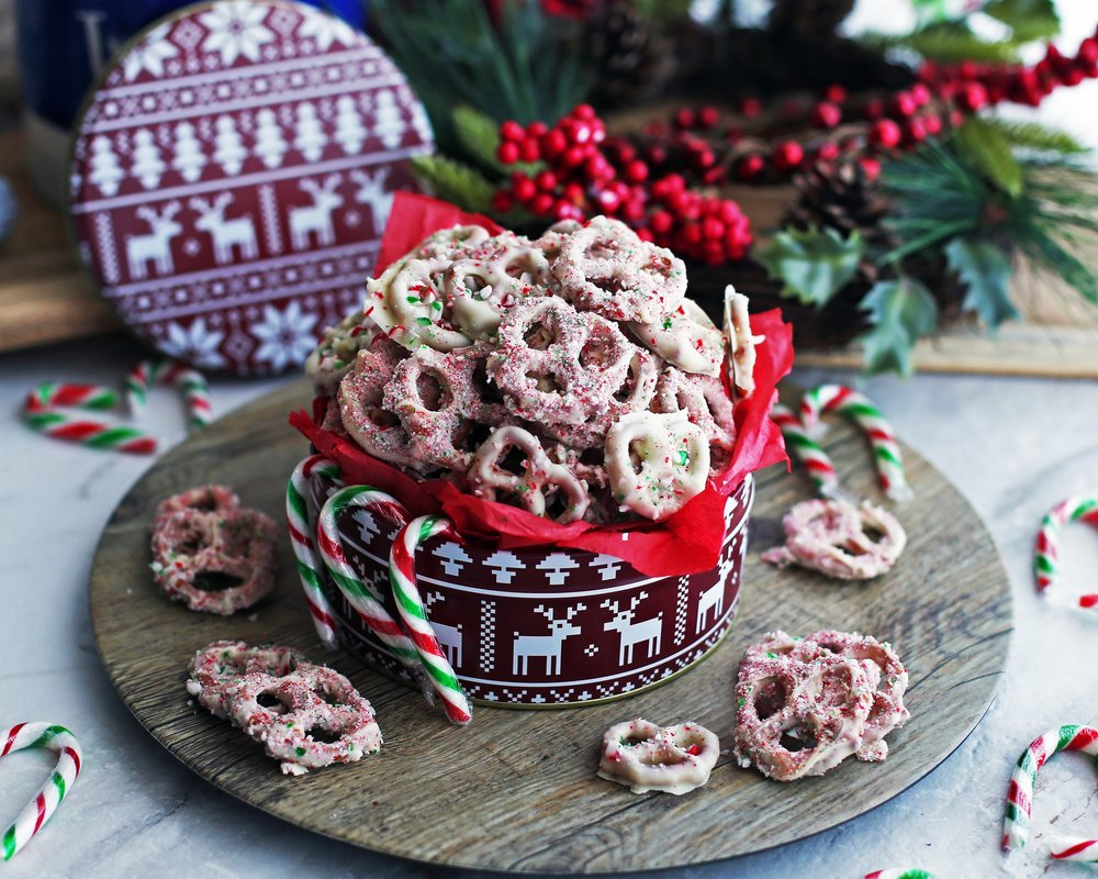 Four-ingredient candy cane chocolate-covered pretzels overflowing in a large red tin.