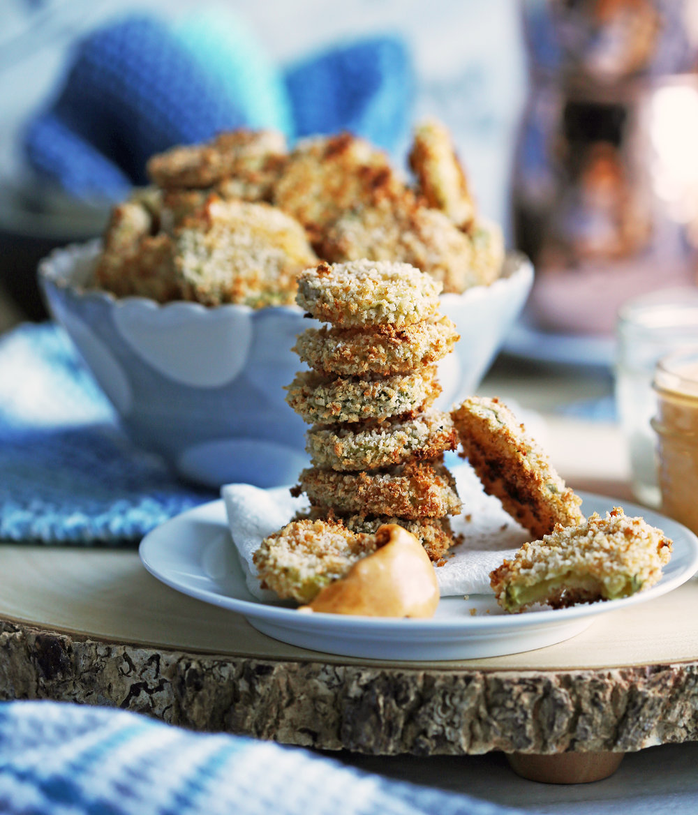 A side view of a stack of crispy oven-fried pickles with a blue bowl of oven-fried pickles in the background.