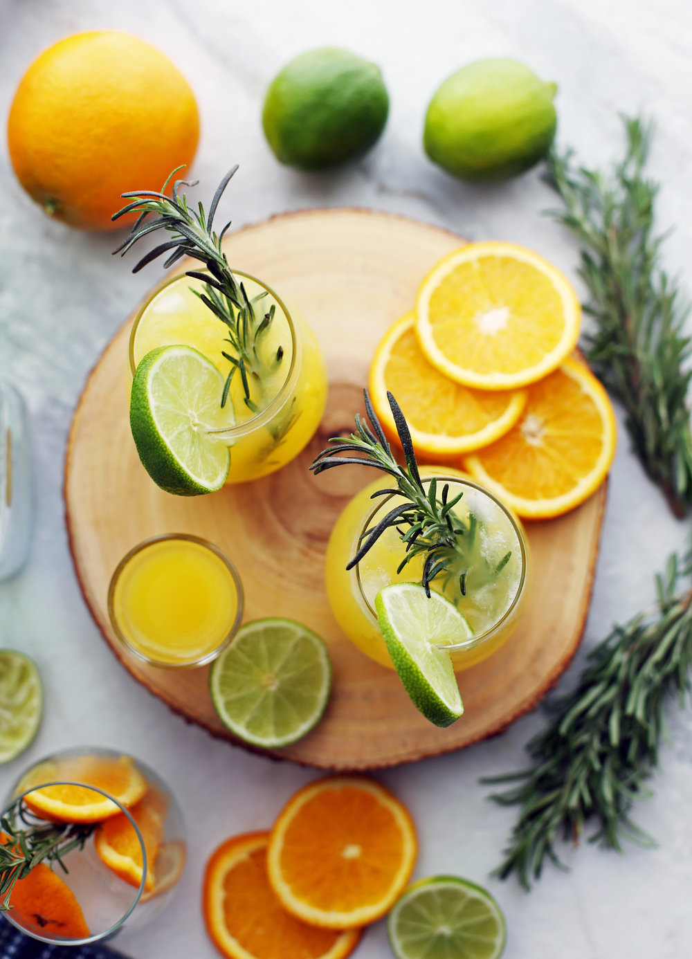 An overhead shot of two glasses of sparkling maple orange vodka spritzers with a sprig of rosemary in each glass.
