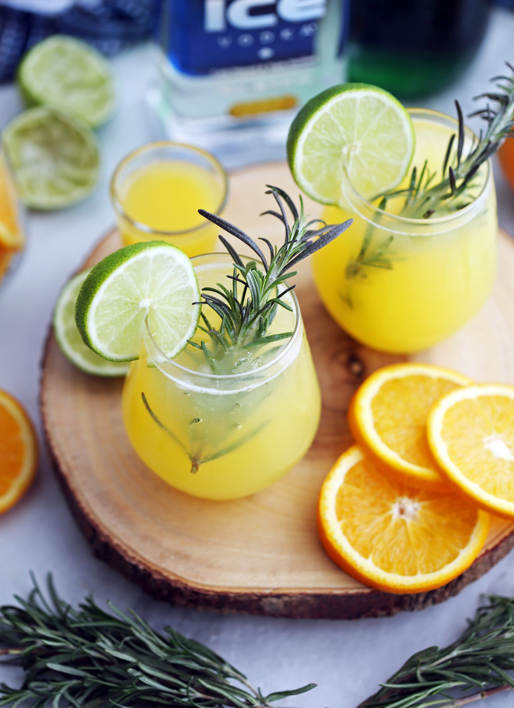 An high-angled view of two glasses of sparkling maple orange vodka with fresh rosemary sprigs, lime slices, and orange slices.