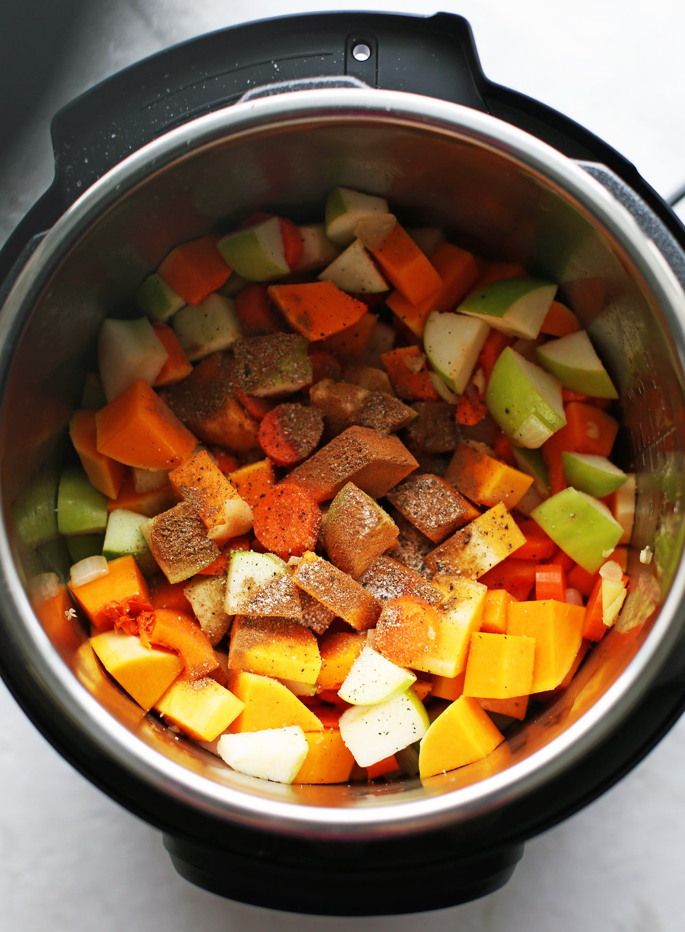 Sautéed onions, ginger, and garlic with chopped butternut squash, granny smith apples, carrots, and spices in the Instant Pot.