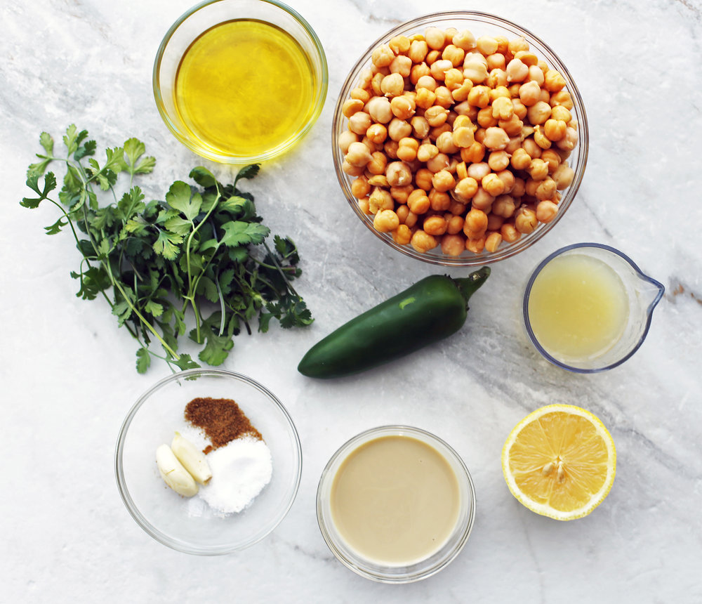 An overhead view of cooked chickpeas, cilantro, jalapeno pepper, tahini, lemon, garlic, olive oil, cumin, and salt.