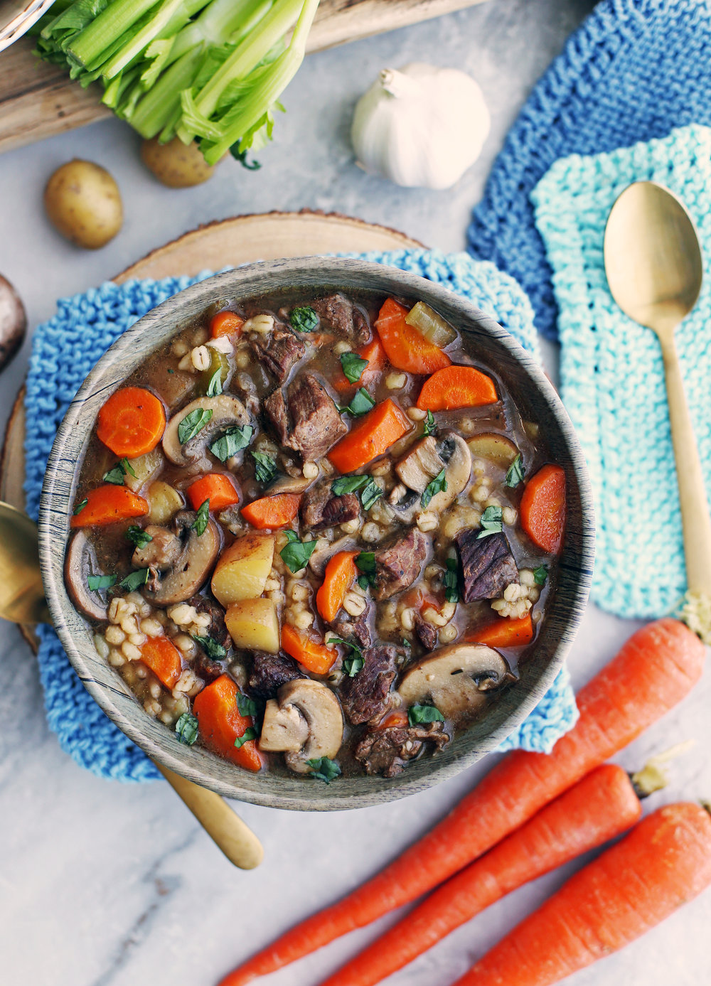 Beef barley mushroom soup with fresh vegetables (e.g. carrots, celery, potatoes, onion) in a bowl.