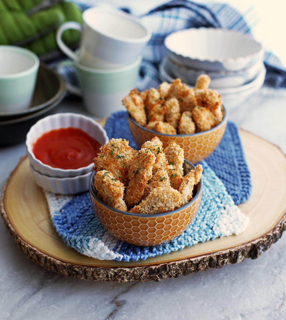 A top angled view of two bowls of baked crispy coconut chicken nuggets with red sauce on the side.