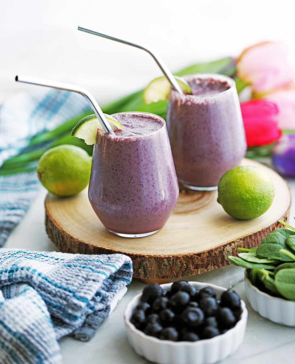Two Blueberry Lime Yogurt Smoothies on a round wooden board, surrounded by limes, blueberries, and spinach.