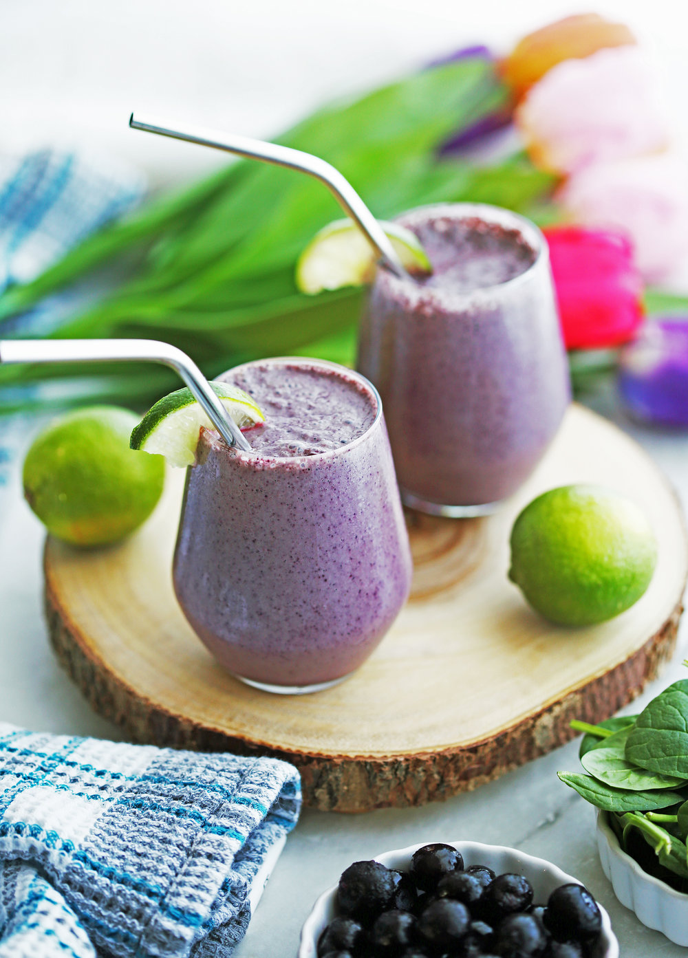 Two purple Blueberry Lime Yogurt Smoothies on a round wooden platter.