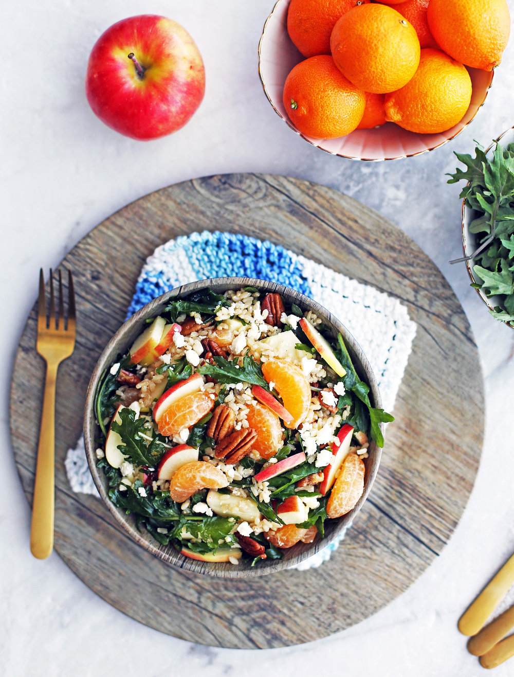 Overhead view of baby kale brown rice salad with feta, apples, and clementines in a wooden bowl, with fork to its side, on a large wooden platter.