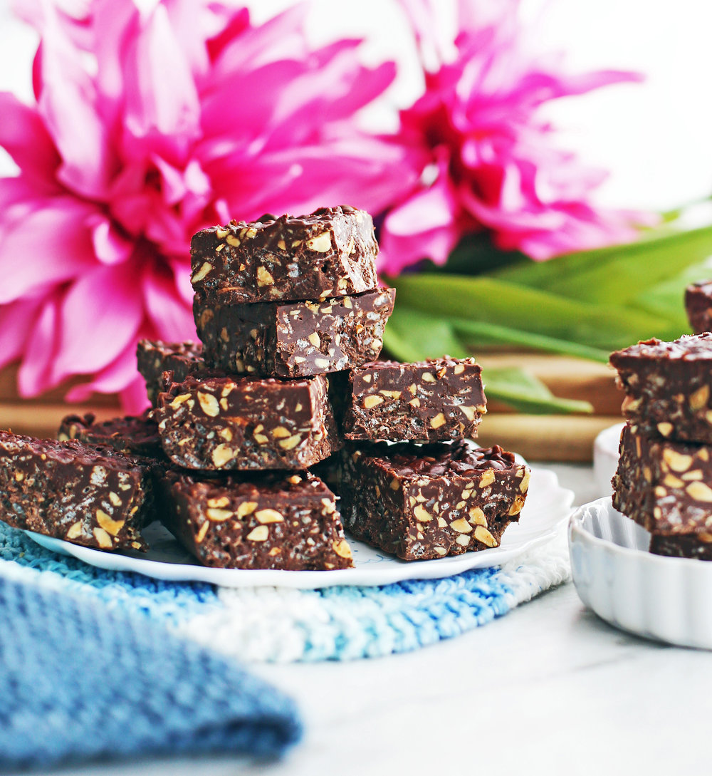 No-bake Peanut Butter Chocolate Crunch Bars stacked in a pyramid on a white plate; pink flowers behind them.