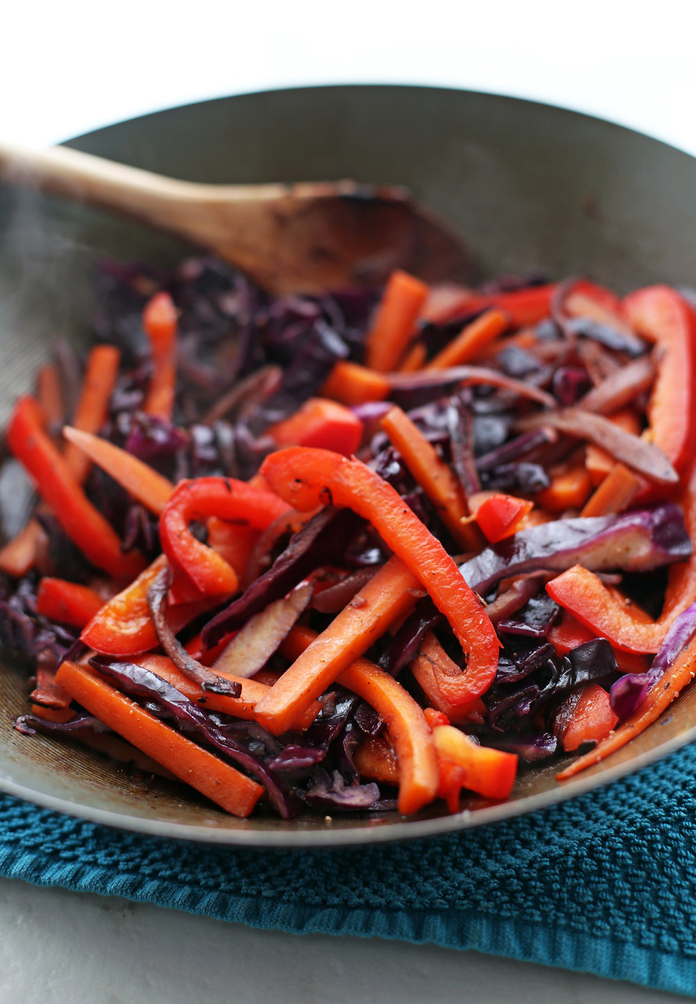 Stir-fried onions, bell pepper, red cabbage, and carrots in a large wok.